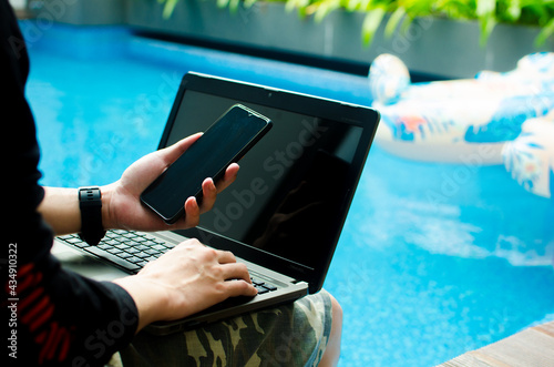 Fotografia Man working on his laptop computer sitting at poolside