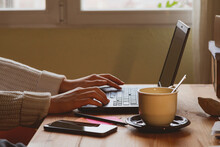 Photograph Of The Desk And Hands Of A Young Caucasian Woman Writing An Email On Her Laptop While Teleworking From Home Early In The Morning In Madrid, Spain.