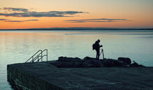 Silhouetted Photographer Taking Shot Of Blacrock Tower At Sunrise On Salthill Beach In Galway, Ireland