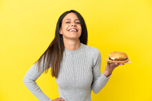 Young Caucasian Woman Holding A Burger Isolated On Yellow Background Posing With Arms At Hip And Smiling