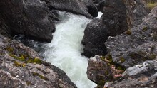 White Foamy Water Stream Rapidly Flowing Downstream Through Boulders