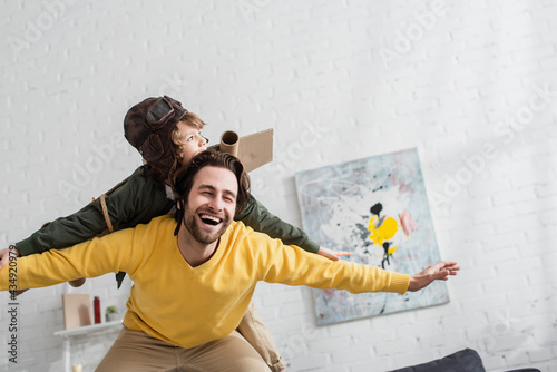 Photo Low angle view of happy dad playing with boy in aviator costume