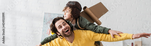 Photo Kid in aviator costume playing with dad at home, banner