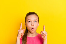 Photo Of Shiny Adorable Small Schoolgirl Dressed Pink T-shirt Pointing Up Fingers Looking Empty Space Isolated Yellow Color Background