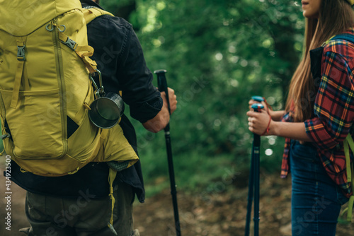 Fotografiet Couple of hikers using trekking poles and wearing backpacks