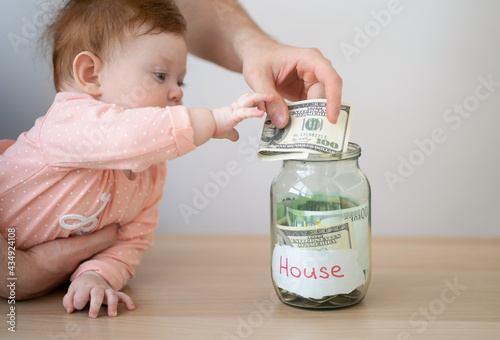 Foto The kid and dad put money in a piggy bank with the inscription - home