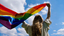Blonde, Lesbian, Woman Holding A Rainbow LGBT Gender Identity Flag On Sky Background With Clouds On A Sunny Day And Celebrating A Gay Parade