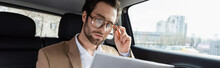 Confident Man Adjusting Glasses And Reading Business Newspaper In Car, Banner