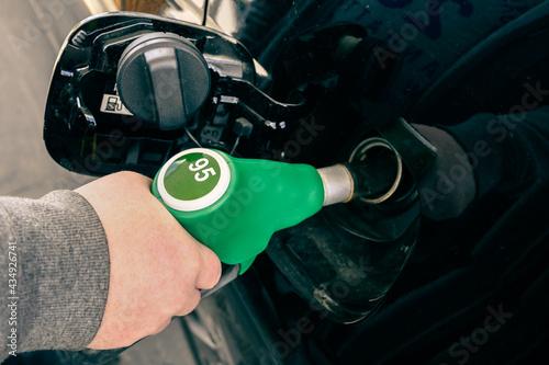 Valokuva A man pumping gasoline fuel in car at gas station.