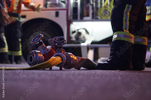 Canvastavla Firefighter at night with fire hose and fire engine in the back