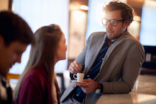 Young Handsome Man Drinking Coffee, Leaned On A Bar, Talking To Attractive Female Sitting