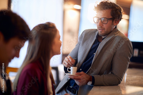 young handsome man drinking coffee, leaned on a bar, talking to attractive female sitting #434938144