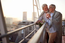 An Elderly Couple Is In Romantic Moments While They Enjoying The View On The City From The Terrace Of Their Apartment. Spouses, Pensioners, Together, Home