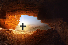 Black Cross With Bright Light In Front Of Dark Cave In The Dry Hostile Desert With Boulders