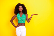 Photo Portrait Of Curious Girl Looking Promoting Keeping Blank Space On Hand Isolated Bright Yellow Color Background