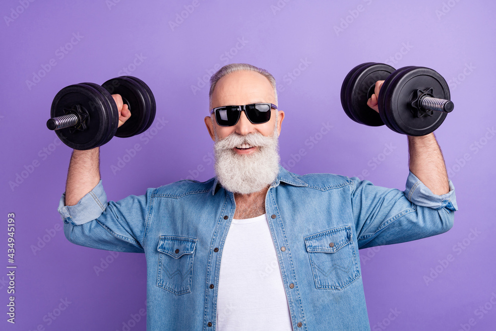 Photo of elderly sportsman bodybuilding muscles strong dumbells isolated over purple color background