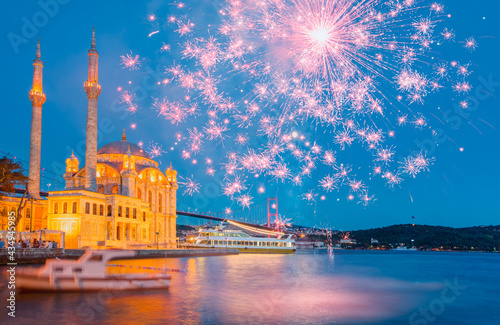 Ortakoy mosque and Bosphorus bridge with  pink fireworks at twilight blue hours Fotobehang