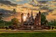 Leinwandbild Motiv Buddha statue and pagoda Wat Mahathat temple with dramatic syk sunset, Sukhothai Historical Park, Thailand