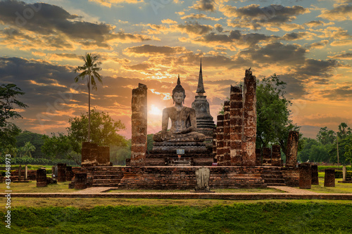 Fotografia Buddha statue and pagoda Wat Mahathat temple with dramatic syk sunset, Sukhothai