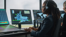 Female Air Traffic Controller With Headset Talk On A Call In Airport Tower. Office Room Is Full Of Desktop Computer Displays With Navigation Screens, Airplane Departure And Arrival Data For The Team.