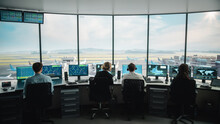 Diverse Air Traffic Control Team Working In A Modern Airport Tower. Office Room Is Full Of Desktop Computer Displays With Navigation Screens, Airplane Departure And Arrival Data For Controllers.