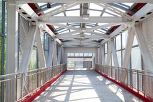 Pedestrian Crosswalk Under Glass Roof Passage In Urban Environment. Overhead Pedestrian Bridge Overpass In Urban Area. Footbridge Tunnel Made From Piles And Glass With Abstract Design