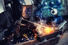 Closeup Industrial Welder At Factory Use Equipment Mask And Tool Weld For Metalwork With Smoke, Fire , Spark