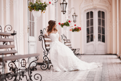 Canvas Beautiful bride is sitting on wooden bench in old city