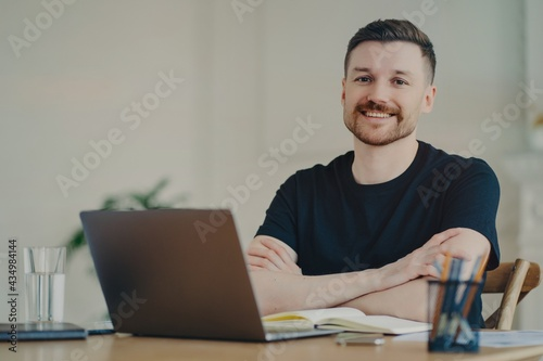 Portrait of happy businessman in casual wear sitting at his workplace in office or home