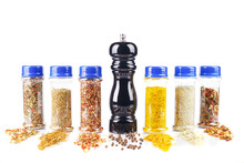 Herbs Spices And Black Pepper Spilling From Spice Jars And Pepper Mill Isolated On White Background