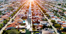 Aerial View Over The Houses Of A Surbubian Community Under The Sunlight. An Idyllic Suburban Town With Garden And Waterway Between Houses 4K