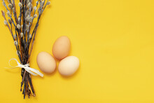 Three Eggs And A Sprig Of Pussy Willow On A Yellow Isolated Background. The Easter Holiday Celebration Concept