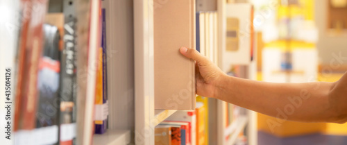 Fotografie, Obraz Book and library, close up hand choosing and picking books from bookshelf in library