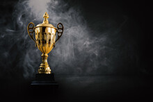 1st Champion Award, The Best Prize And Winner Concept, Championship Cup Or Winner Trophy On Wood Table On Dark Wall And White Smoke Background