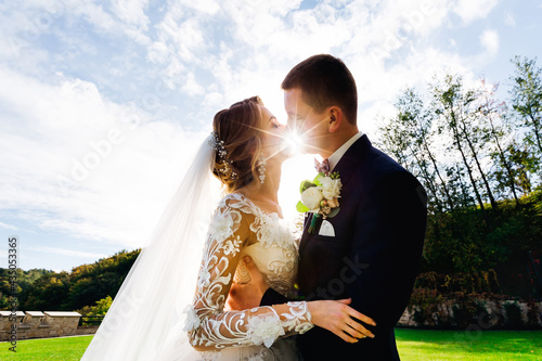 Foto The bride and groom stand in a beautiful green garden on a warm summer day