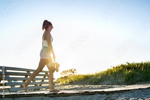 Canvas Print Summer evening walk on the beach boardwalk at dawn
