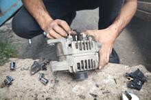 Man Repairs Car Alternator. Service Center