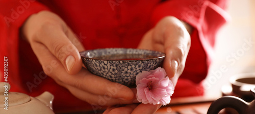 Canvastavla Guest holding cup of freshly brewed tea and sakura flower during traditional ceremony at table indoors, closeup