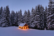 Leinwandbild Motiv Wooden hut on the lawn covered with snow. The lamps light up the house at the evening time. Winter landscape. Mystical night. Mountains and forests. Wallpaper background.