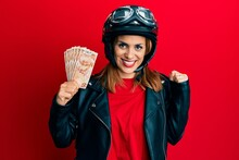 Hispanic Young Woman Wearing Motorcycle Helmet Holding 50 Turkish Lira Screaming Proud, Celebrating Victory And Success Very Excited With Raised Arm