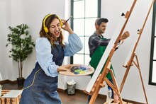 Two Hispanic Students Smiling Happy Painting At Art School. Standing And Dancing With Smile On Face.