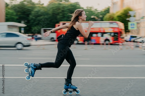 Carta da parati Young fit woman on roller skates with wheels rollerblades during summer day on busy road with transport leads active lifestyle wears black sportsclothes breathes fresh air