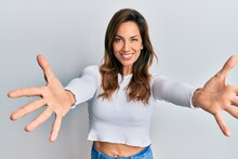 Young Latin Woman Wearing Casual Clothes Looking At The Camera Smiling With Open Arms For Hug. Cheerful Expression Embracing Happiness.