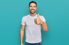 Handsome Man With Beard Wearing Casual White T Shirt Doing Happy Thumbs Up Gesture With Hand. Approving Expression Looking At The Camera Showing Success.