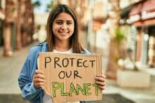 Young Latin Girl Smiling Happy Holding Protect Our Planet Banner At The City.