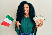 Middle Age African American Woman Holding Italy Flag And Euros Banknotes Celebrating Crazy And Amazed For Success With Open Eyes Screaming Excited.
