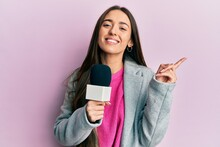 Young Hispanic Girl Holding Reporter Microphone Smiling Happy Pointing With Hand And Finger To The Side