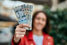 Young Hispanic Woman Smiling Happy Holding Peruvian Sol Banknotes At The City.
