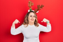 Middle Age Caucasian Woman Wearing Cute Christmas Reindeer Horns Showing Arms Muscles Smiling Proud. Fitness Concept.
