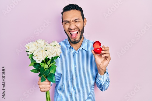 Obraz na płótnie Hispanic man with beard holding bouquet of flowers and engagement ring sticking tongue out happy with funny expression